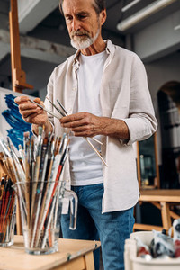 Male artist choosing paintbrush