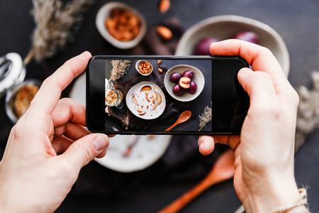 Hands hold smartphone and take picture of morning porridge with almond and sliced plum  Food photography concept