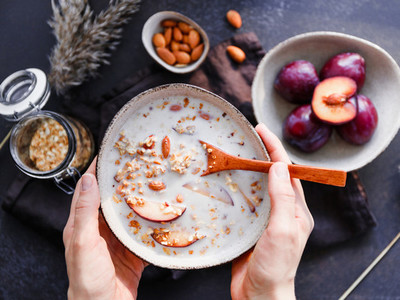 Hands hold a bowl of morning porridge with almond and sliced plum Healthy energy breakfast top view
