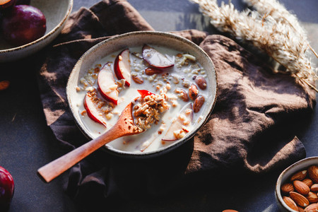 Morning granola with vegetarian cashew milk  almond and sliced plum  Healthy energy breakfast