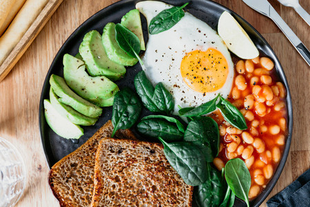 Healthy breakfast lunch at home or cafe with fried egg  avocado  toasts  beans and fresh spinach  Top down view