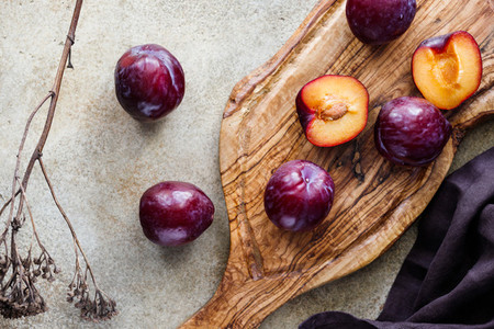 High angle view of fresh purple plum on a textured wooden cutting board