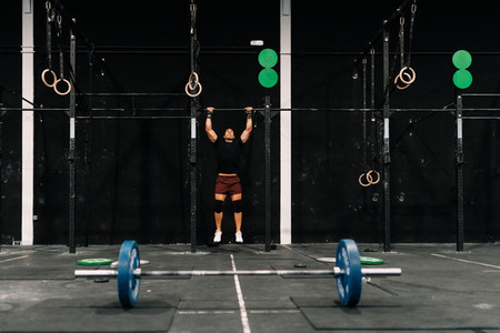 Young muscular man training on bar in a gym