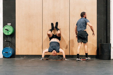 Two men training on floor in a gym doing handstand wall