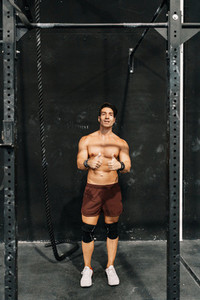 Young muscular man showing thumbs up in the gym
