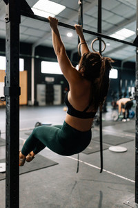 Young woman training on bar in a gym