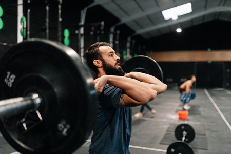 Young male weightlifter exercising in gym