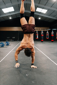 Young man training on floor in a gym doing handstand walk
