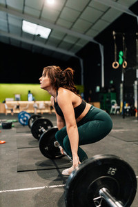 Strong female weight lifter preparing for lift in gym