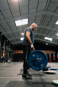Adult bald man weightlifter exercising in gym