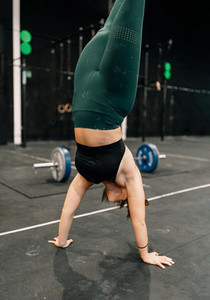 Young woman training on floor in a gym doing handstand walk