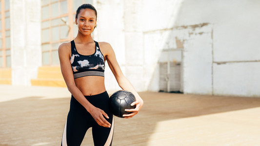 Smiling woman with medicine ball