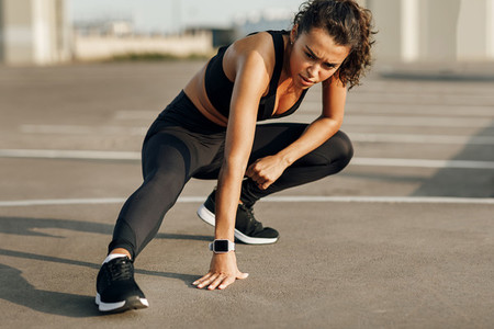 Young sport woman stretching leg