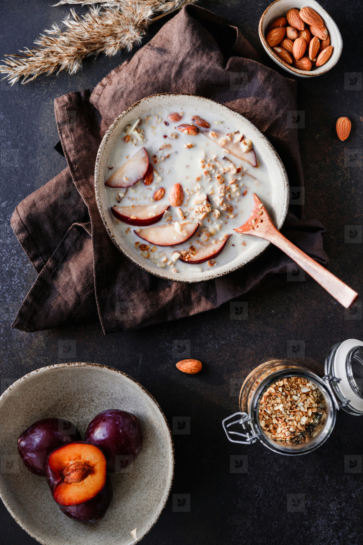 High angle view of morning granola with vegetarian cashew milk  almond and sliced plum  Healthy energy breakfast