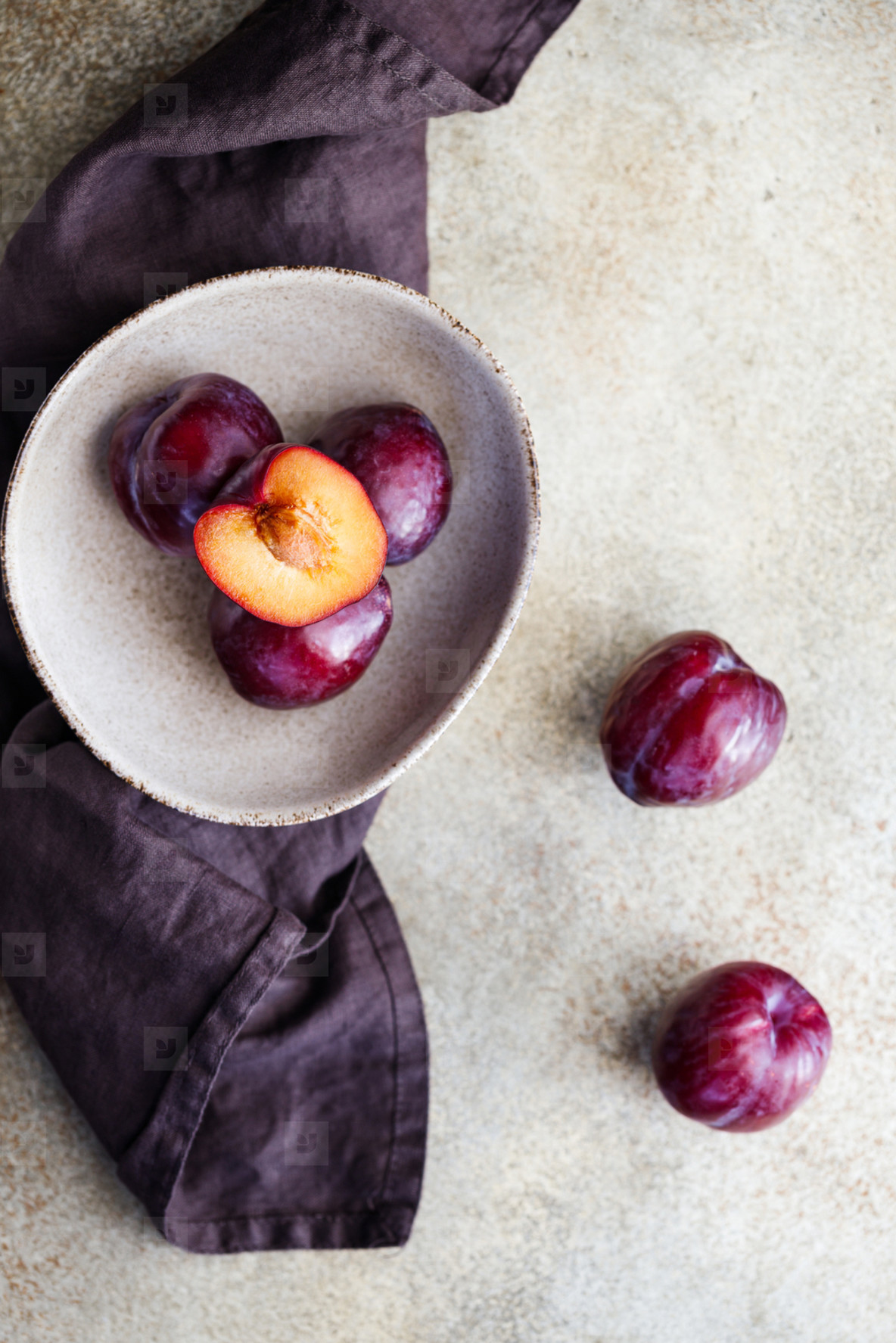 Top view of purple plum in a ceramic bowl on a beige textured background