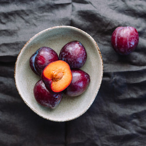 Top view of purple plum in a ceramic bowl on a  dark background