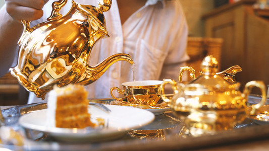 Close up of woman hand pouring golden luxury teapot set in the c