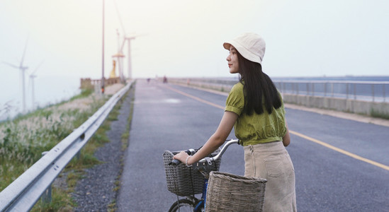 Young asian millennial woman with bicycle feeling relax while tr