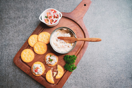 Top view of tasty tuna spread with crackers on wooden tray and b
