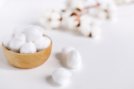 Cotton balls for cleansing with natural cotton flowers on white