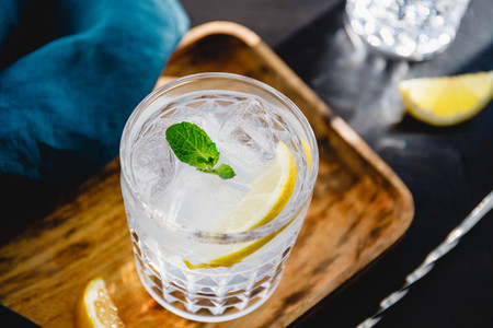 Refreshing cold summer cocktail with soda water lemon and ice cubes on a wooden tray