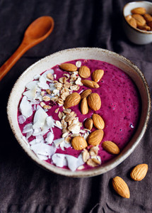 Purple berry smoothie with coconut flakes oats and almond nuts