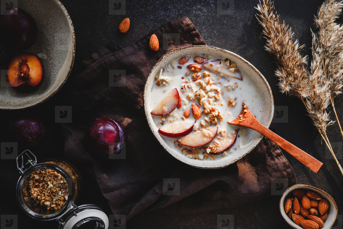 High angle view of morning porridge with almond and sliced plum  Healthy energy breakfast