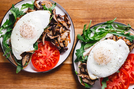 Top view of two sandwiches with fresh arugula fried shiitake mushroom shallot onion egg served with tomatoes