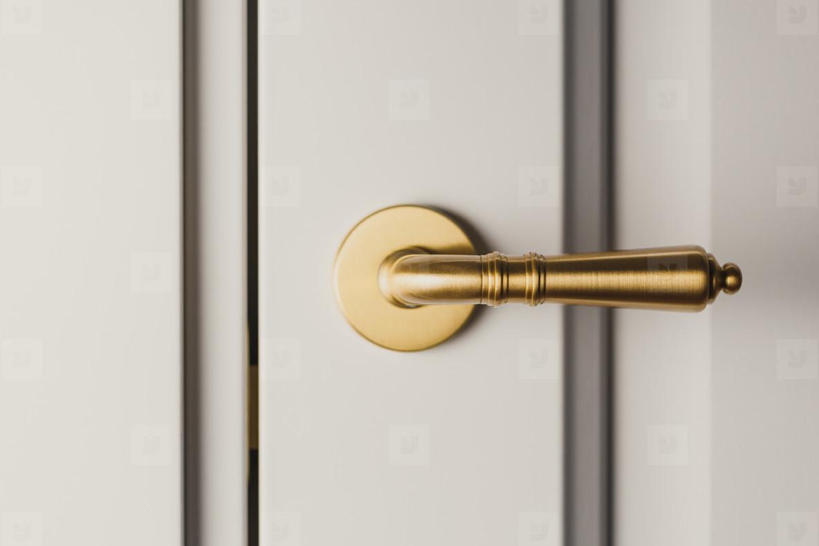 Brushed gold modern design in vintage style door handle on a white door