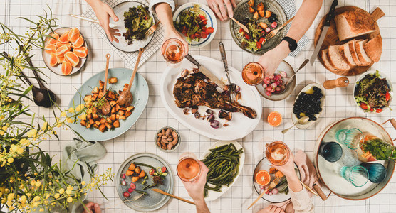 Peoples hands with glasses of wine over table with snacks