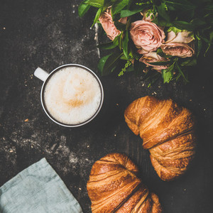 Cup of cappuccino fresh croissants and flowers square crop