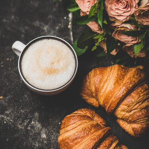 Cup of cappuccino  fresh croissants and pink flowers  square crop