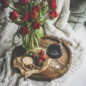 Red wine snacks and tulips over knitted blanket square crop