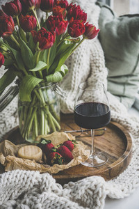 Glass of red wine snacks and spring red tulips