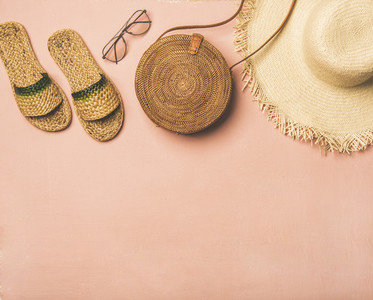 Variety of summer apparel items over pastel background  copy space