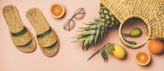 Summer apparel set and fresh fruits over pastel pink background