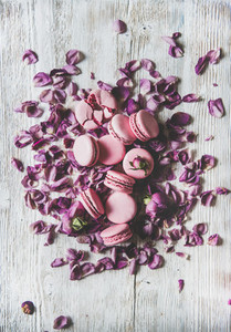 Sweet macaron cookies heap and rose buds and petals