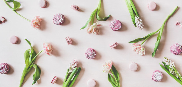 Macaron cookies marshmallows and flowers over pink background top view