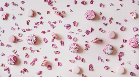 Flat lay of macaron cookies  marshmallows and petals over pink background