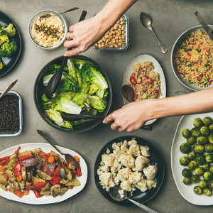 Healthy vegan dishes and woman hands taking salad  square crop