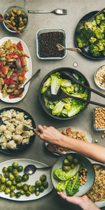 Healthy vegan dishes and woman hand taking cauliflower  narrow composition