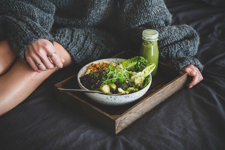 Healthy vegan bowl on tray and woman in sweater