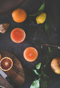 Flat lay of orange juice in glasses and fresh fruits