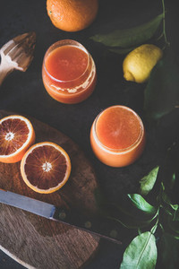 Orange juice in glasses and fresh citrus fruits top view