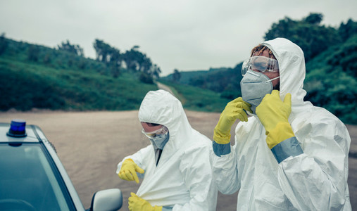 Two young people putting on bacteriological protection suits