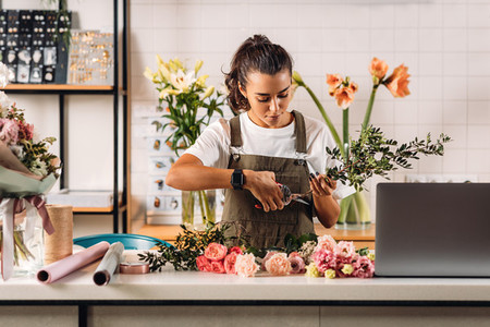 Female florist cutting stems