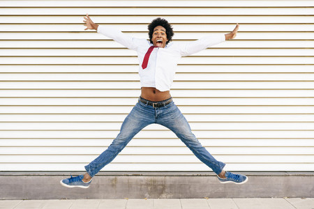 Black Businessman jumping outdoors  Man with afro hair