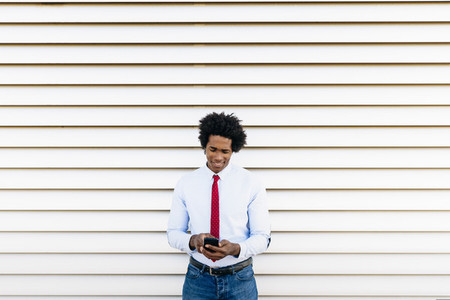 Black Businessman using a smartphone with a white blinds background