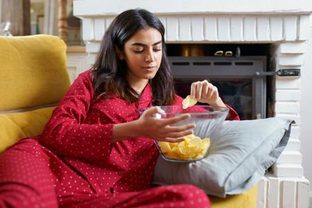 Persian woman at home watching TV eating chips potatoes