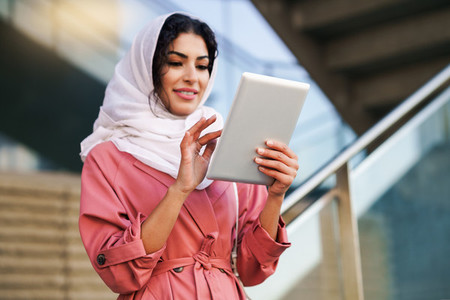 Young Arab woman wearing hijab using digital tablet outdoors